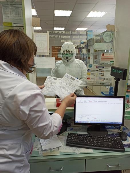 Фармацевт аптеки №31 выдаёт медсестре О.А.Вылегжаниной лекарства по рецепту для больного коронавирусом.